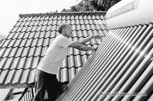 【涂华明正在检查太阳能热水器】