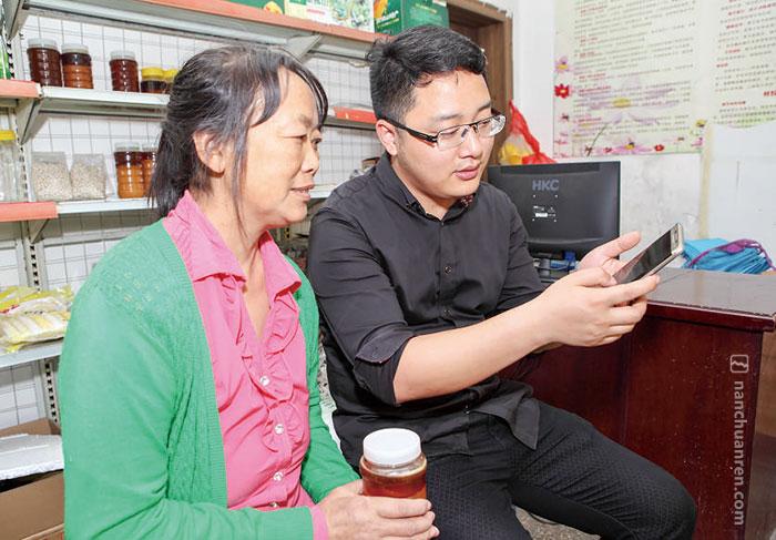 """【 5月6日,韦鸿正在向商家介绍""""好耍南川""""微信平台,希望和商家合作,将商家的玄参蜂蜜放到平台上销售。】"""