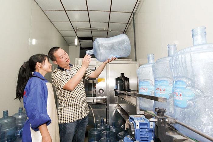 【8月18日,时荣恒正在监督工作人员给饮水桶消毒】