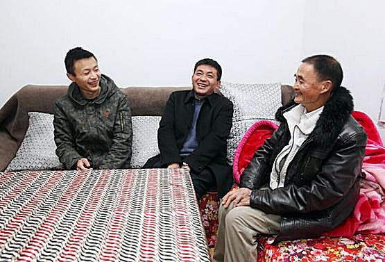 【好心人胡开明(中)看望阳达兴与爷爷】
