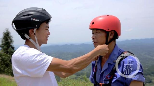 起飞前彭胜帮父亲系好安全帽