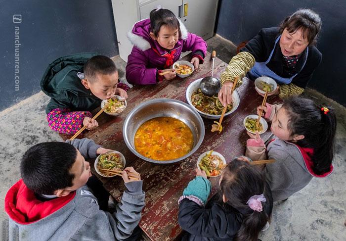 午饭时间,黄先群把饭菜做好摆上桌,招呼孩子们围坐一起共进午餐。