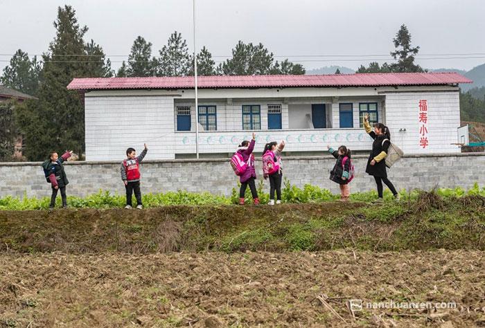 黄先群在放学后和孩子们道别