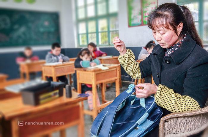 黄先群利用自习时间为孩子缝补书包肩带