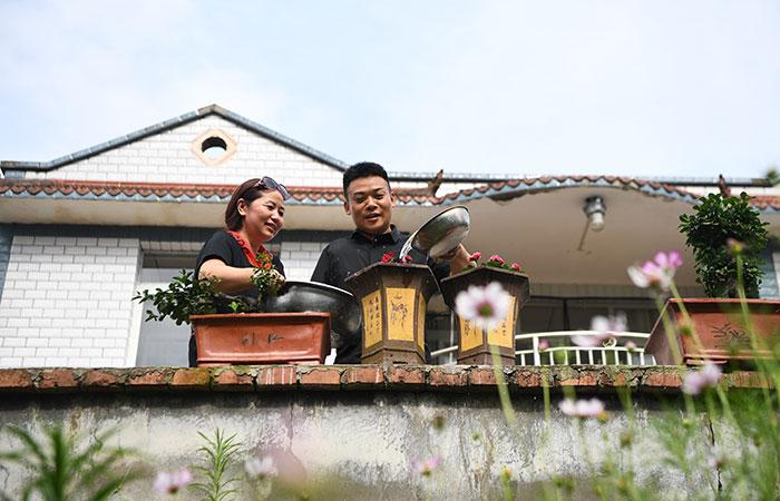 刘毅和妻子卢开在自家院子里给花浇水